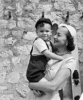 Sonriendo mientras sostiene a su hijo en sus brazos