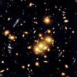 lensa gravitasi. Gambar dari Teleskop Ruang Angkasa Hubble ini menunjukkan beberapa obyek yang terbentuk dengan putaran yang biru yang sebetulnya adalah beberapa tampilan dari galaksi yang sama. Mereka sudah digandakan oleh efek lensa gravitasi kelompok galaksi yang berwarna kuning, bulat panjang dan spiral di dekat pusat foto. Pelensaan gravitasi dihasilkan oleh bidang gravitasi kelompok yang luar biasa masif sehingga mampu melengkungkan cahaya. Beberapa akibatnya adalah memperbesar ukuran obyek yang dilensakan, menjadikan terang dan mengubah tampilan benda yang lebih jauh.