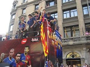 The FC Barcelona team take an open-top bus aro...