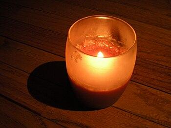 English: An orange candle burning in a dark en...