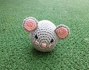 A little gray mouse in crochet with a bell ins...