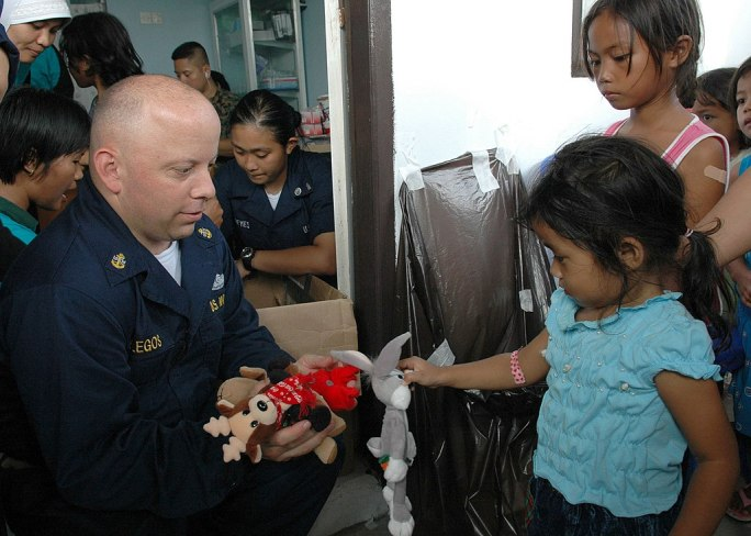 US Navy 060816-N-3714J-094 Navy Chief Hospital Corpsman Chris Gallegos of San Diego, a member the Medical Treatment Facility aboard the U.S. Naval hospital ship USNS Mercy (T-AH 19), distributes stuffed animals to children