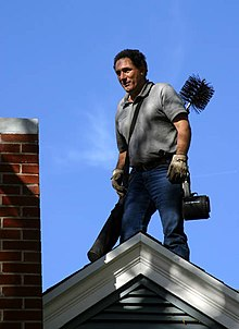 A caucasian man of about forty stands on the ridge of a modern house next to a red brick chimney. He is in jeans and a polo shirt and wears leather safety gloves.On his back is a standard chimney sweeping brush and poles.
