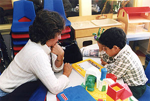 A special education teacher assists one of her...