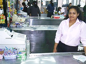 A cashier at her register in a grocery store i...