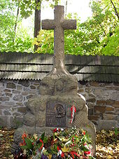 "A stone cross atop a large rock. A plaque mounted on the rock reads: ""Ostaszkow, Starobielsk, Kozielsk, Katyn 1940"", followed by ""Zwiazek Sybrakow""."