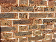 Tuckpointing: here red mortar is used. The white fillets are laid out at regular spacing, which does not always coincide with the rough spacing of the joints.