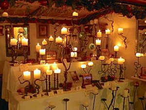 A collection of lit candles on ornate candlesticks