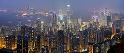 A panorama overlooking the skyscrapers of Hong Kong at night, with Victoria Harbour in the background