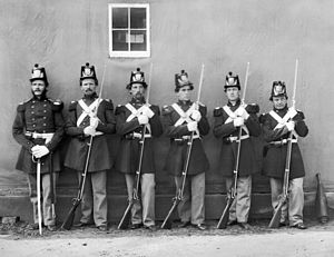 Five Marines with fixed bayonets, and their NC...
