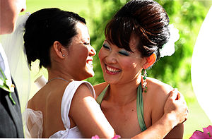 The bride (in white) embraces her bridesmaid.