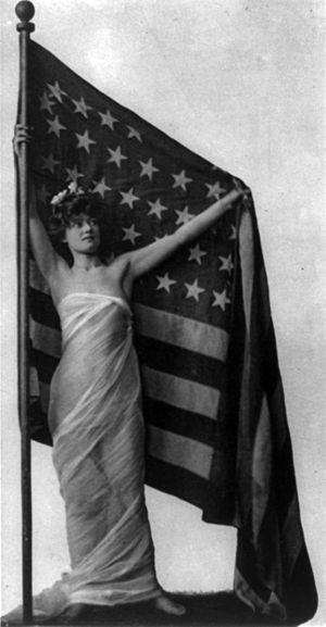 English: Woman standing, as America, facing sl...