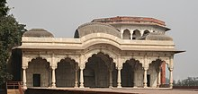 Low, white building with ornate pillars and arches