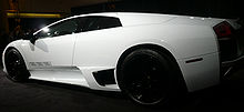 A profile view of a low-slung white sports car. Three small black glyphs representing the Gianni Versace design house are visible on the door.