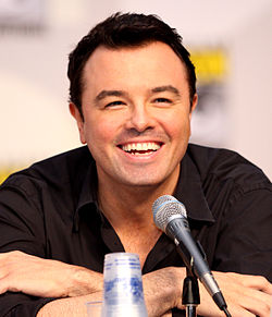 A man (Seth MacFarlane) with black hair, and tan skin with a black shirt on, leans forward while laughing into a microphone.