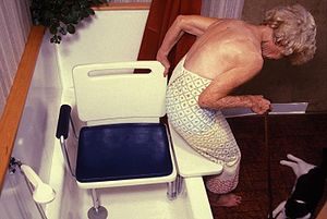 an elderly woman exiting or entering a bath tu...