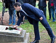 Alexis Tsipras laying down red roses at the Kaisariani Memorial.