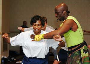 Fitness trainer Billy Blanks shows a female wo...