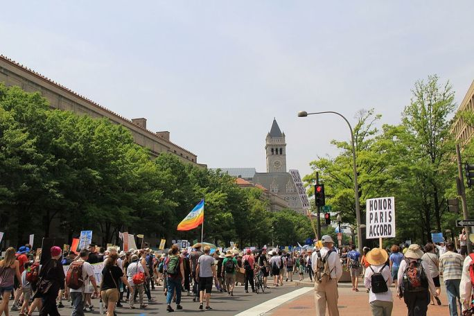 People's Climate March 2017 in Washington DC 33 - Crowd marching toward Trump Hotel with rainbow flag and sign Honor Paris Accord