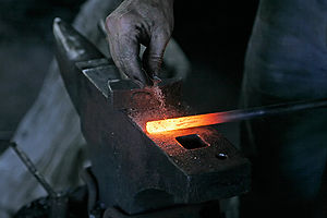 A blacksmith removing rust with sand prior to ...