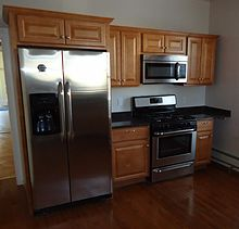 220px Newly renovated kitchen with cabinets refrigerator stove and hardwood floor Small Space Kitchen Solutions