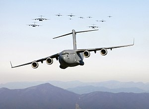 Thirteen C-17 Globemaster III aircraft fly ove...