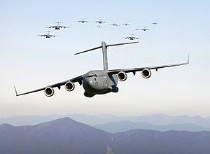 Thirteen C-17 Globemaster III aircraft fly ove...
