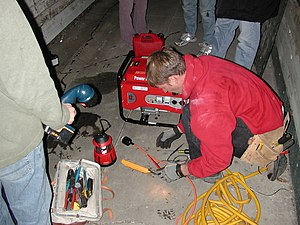 An electrician hooking up a generator to a hom...