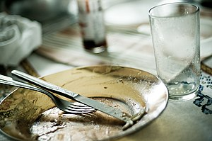 Used cutlery: a plate, a fork and knife, and a...