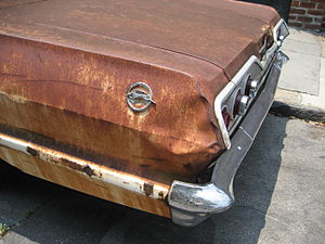 Detail of rusty 1960s Chevy Impala parked in t...
