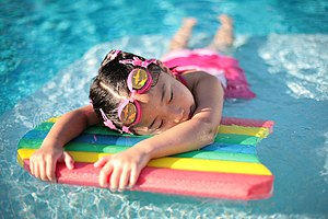 English: A young girl taking a break in a swim...