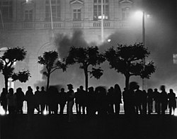 A line of people silhouetted against a building, with a plume of smoke rising behind the people.