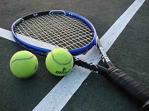 Shot of a tennis racket and two tennis balls o...
