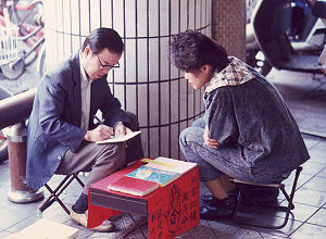 Street fortune teller consults with client in ...