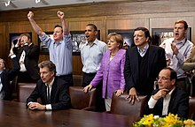 Prime Minister David Cameron of the United Kingdom, President Barack Obama, Chancellor Angela Merkel of Germany, José Manuel Barroso, President of the European Commission, President François Hollande of France and others react emotionally while watching the overtime shootout of the Chelsea vs. Bayern Munich Champions League final, in the Laurel Cabin conference room during the G8 Summit at Camp David, Maryland, May 19, 2012. Cameron raises his arms triumphantly as the Chelsea team wins their first Champions League title in the overtime shootout.