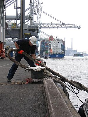 English: A mooring man putting a line on a bol...
