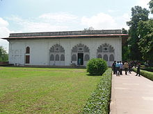 Simple white building, with persons on walkway
