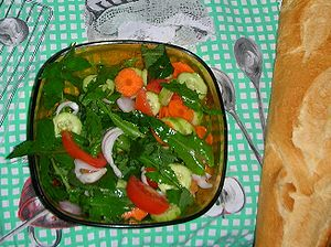 English: Green salad with carrot, cucumber, on...