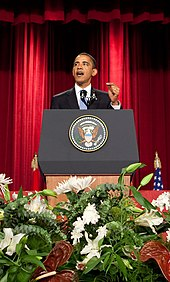 "President Obama stands at a podium delivering a speech on ""A New Beginning"" at Cairo University on June 4, 2009"