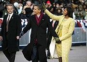 Barack en Michelle Obama Houdt handen en Glimlach tijdens Het Lopen;  zwaait ZE Naar een menigte.  Ze Draagt Een gouden geborduurde jurk en jas;  HIJ Draagt Een zwarte jas en bordeaux sjaal.  Een Serieuze man in Een donker pak horloges in de Buurt.