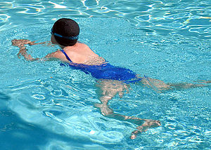 A breaststroke swimmer, in a hotel swimming po...