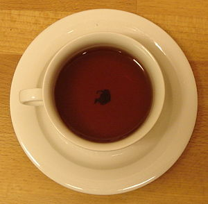English: A teacup on a wooden table. The leave...