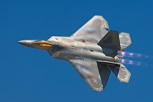 F-22 Raptor banking left in-flight, showing the top view of the aircraft. The engines with afterburners emit a pinkish glow. Aircraft mostly gray, apart from the gold cockpit window, with hints of bluish condensation on the wings.