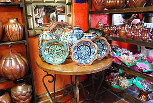 English: Painted copperwork vases and plates o...