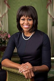 Michelle Obama naar Voren, Lachend, Gekleed in zwarte Kleding en Enkele streng parelsnoer roest blote rechter onderarm en Beide handen op Een brokaten sofa armleuning.