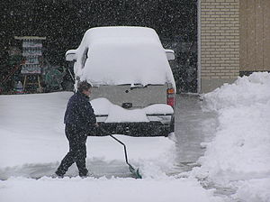 Neighbor shoveling snow from their driveway du...