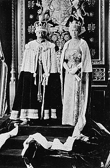 Late-middle-aged couple in crowns and ermine capes stand on a dais
