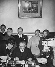 Stalin (in background to the right) looks on as Molotov signs the Molotov-Ribbentrop Pact, August 24, 1939.
