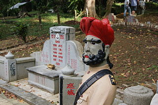 A statue of a sepoy guarding a tomb in Bukit Brown Cemetery