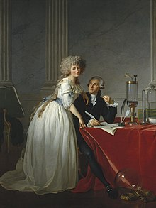 Full-length portraits of a man and a woman. The man is seated at a table covered with a bright red cloth, looking up at the woman, and she is looking out at the viewer. They occupy the bottom half of the painting, while the top half resembles marble and pillars. She is wearing a white dress with a blue sash and he is wearing a dark colored suit. Glass chemistry equipment sits on the table and on the floor.